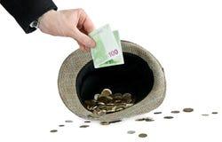 Mens die een geld opneemt in hoed Stock Afbeelding