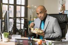 Mens die een Gezonde Lunch eten bij Zijn Bureau royalty-vrije stock foto