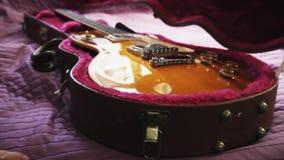 Mens die een gitaar terugtrekken uit geval stock video