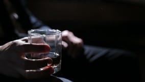 Mens die een glas whisky in zijn rechts houden stock footage