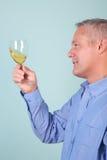 Mens die een glas witte wijn houdt stock afbeelding