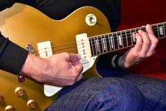 Mens die een gouden hoogste elektrische gitaar spelen P90 bestelwagens, lichaam en halsdetails: Knoppen, rozehout fretboard, scha stock afbeeldingen