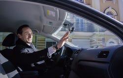 Mens die een hand golven aan zijn vriend, uit auto, dag, openlucht Stock Fotografie