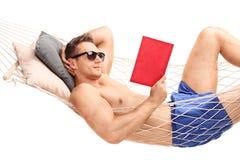 Mens die in een hangmat liggen en een boek lezen stock afbeelding