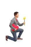 Mens die een hart gevormd hoofdkussen en bloemen houdt Royalty-vrije Stock Afbeeldingen