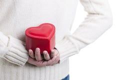Mens die een hart gevormde doos verbergt Royalty-vrije Stock Afbeeldingen