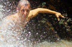 Mens die een het ontspannen douche nemen onder waterval buiten Stock Fotografie