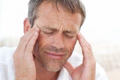 Mens die een hoofdpijn heeft thuis Stock Afbeeldingen