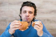 Mens die een hotdog en shawarma eten die gelijktijdig in koffie een zitten royalty-vrije stock foto's