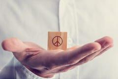 Mens die een houten blok met het vredesteken houden Stock Afbeeldingen