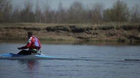 Mens die in een kano roeien Het roeien, canoeing, het paddelen Opleiding kayaking Volgend schot Langzame Motie stock footage