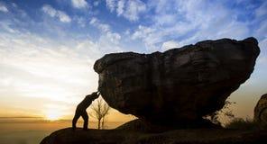 Mens die een kei op een rots duwen royalty-vrije stock afbeeldingen