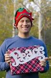 Mens die een Kerstmisgift en een vredesteken houden Stock Foto