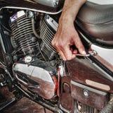 Mens die een klassieke motorfiets in hdr herstellen stock afbeelding