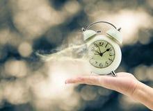 Mens die een klok in zijn hand en verloren tijd houdt Royalty-vrije Stock Afbeeldingen