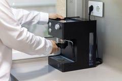 Mens die een koffiehandvat in een koffiemachine houden op een lijst stock foto's