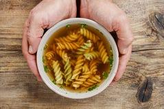Mens die een kom soep houden. Stock Afbeeldingen