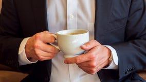 Mens die een kop van koffie met room in witte ceramische kop, gekleed in wit overhemd en zwart pak houden en een wa dragen stock afbeelding