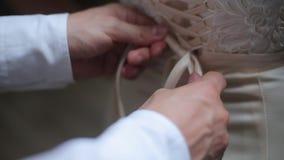 Mens die een korset op de het huwelijkskleding van de bruid binden stock footage
