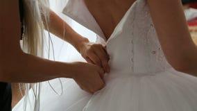 Mens die een korset op de kleding van het bruid` s huwelijk binden stock videobeelden