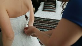 Mens die een korset op de kleding van het bruid` s huwelijk binden stock video