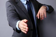 Mens die een kostuum dragen die handen aanbieden te schudden Stock Afbeelding