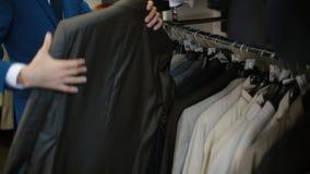 Mens die een kostuum kiezen bij kledingsopslag stock video