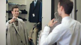 Mens die een kostuum kiezen bij kledingsopslag stock videobeelden