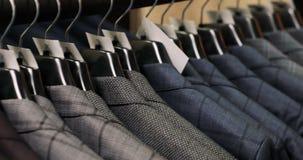 Mens die een kostuum kiezen bij kleermakers` s winkel stock footage
