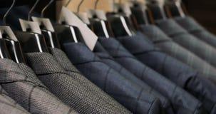Mens die een kostuum kiezen bij kleermakers` s winkel stock videobeelden