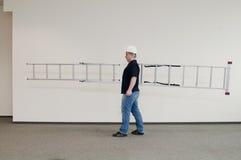 Mens die een ladder draagt stock afbeeldingen