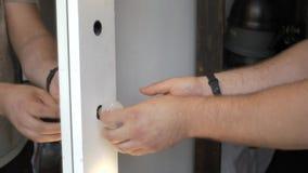 Mens die een lage energiecfl gloeilamp passen om een ouderwetse wolfram gloeiende gloeilamp te vervangen stock videobeelden