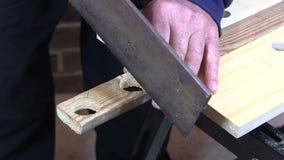 Mens die een lijn en een knipsel trekken een stuk van hout met een zaag stock footage