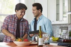 Mens die een maaltijd, zijn vriend voorbereiden die een digitale tablet houden royalty-vrije stock afbeeldingen