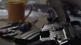 Mens die een machinegeweer herstellen Lijst met hulpmiddelen voor reparatie van wapens Militair geweer stock video