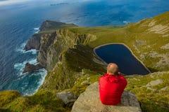 Mens die een meer in een heuvel op Achill-eiland, Co bekijken mayo Stock Fotografie