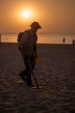 Mens die een metaaldetector op het strand met behulp van Royalty-vrije Stock Foto