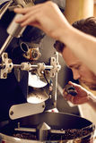 Mens die een moderne koffie roosterende machine in werking stellen en ruiken Royalty-vrije Stock Foto