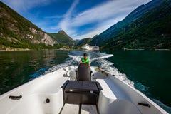 Mens die een motorboot drijven Geirangerfjord, Mooie Aard Noorwegen De vakantie van de zomer royalty-vrije stock fotografie