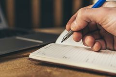 Mens die in een notitieboekje, planningsmonden met laptop op achtergrond schrijven royalty-vrije stock afbeeldingen
