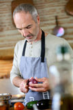 Mens die een oignon in keuken snijden Royalty-vrije Stock Fotografie