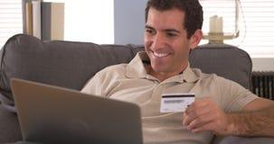 Mens die een online aankoop met laptop maakt stock fotografie
