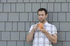 Mens die een oranje koffiekop met twee handen met een grijze achtergrond houden Royalty-vrije Stock Afbeelding