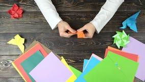 Mens die een origamivos vouwen stock video