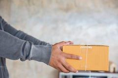 Mens die een pakket leveren Stock Afbeeldingen