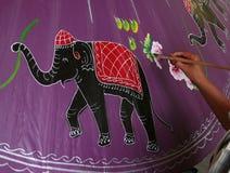 Mens die een paraplu schildert Stock Foto