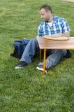 Mens die een picknick buiten in het gras hebben Royalty-vrije Stock Fotografie