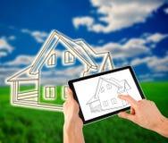 Mens die een plan van zijn huis trekken op de tablet Stock Fotografie