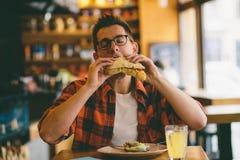 Mens die in een restaurant eten en van heerlijk voedsel genieten stock afbeeldingen