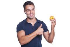 Mens die een rode appel houdt en o.k. teken maakt Stock Fotografie